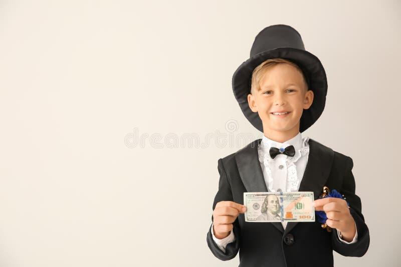 Leuk weinig tovenaar die truc met geld op witte achtergrond tonen royalty-vrije stock afbeeldingen