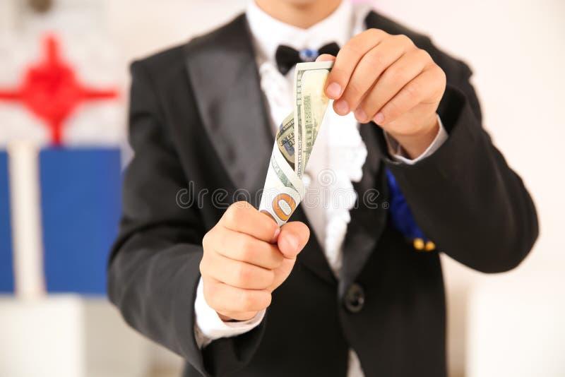 Leuk weinig tovenaar die truc met geld tonen binnen, close-up royalty-vrije stock fotografie