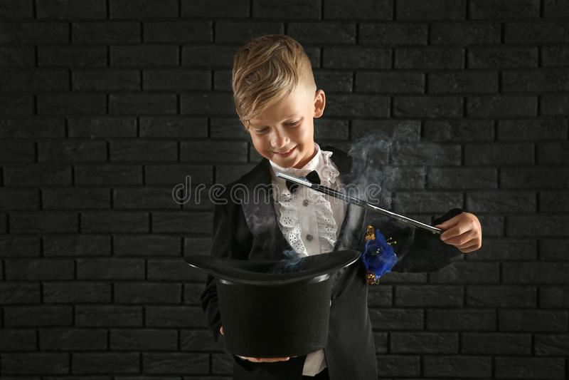 Leuk weinig tovenaar die truc met hoed tonen tegen donkere bakstenen muur stock afbeelding