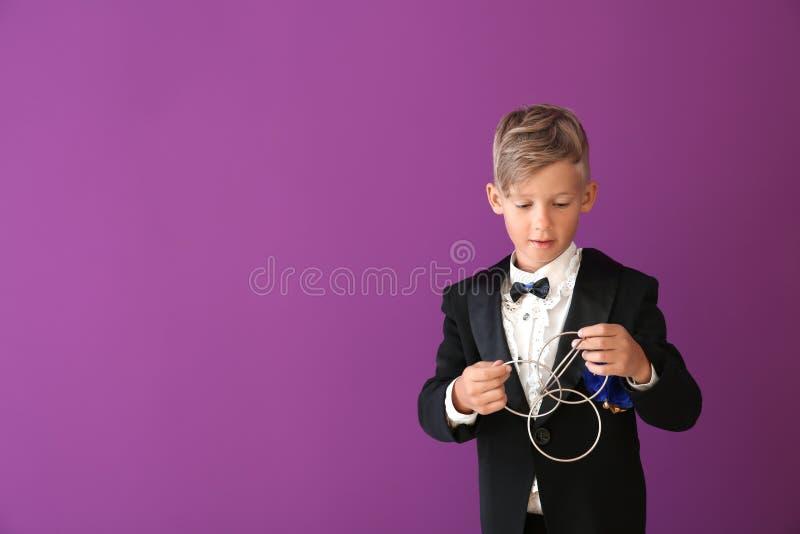 Leuk weinig tovenaar die truc met ringen op kleurenachtergrond tonen stock fotografie