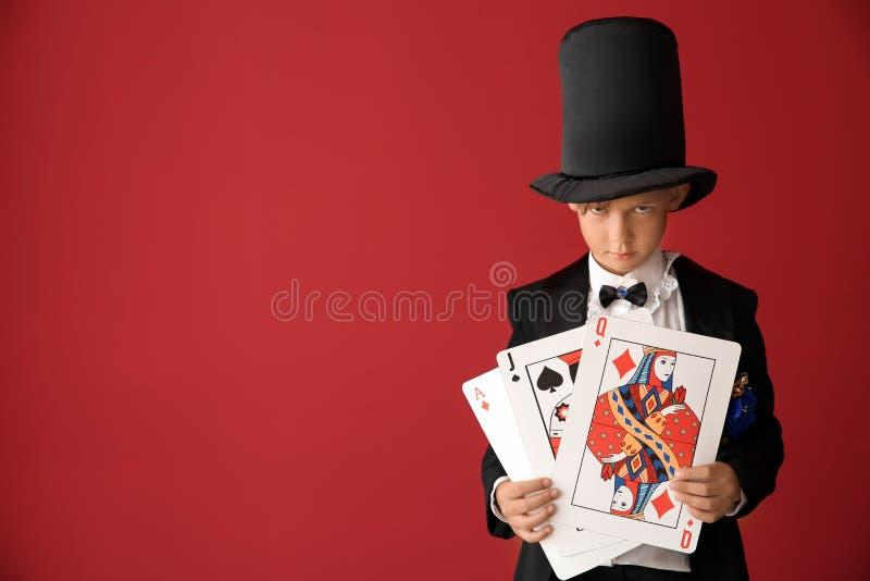 Leuk weinig tovenaar met kaarten op kleurenachtergrond stock afbeelding