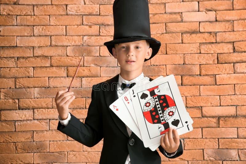 Leuk weinig tovenaar met kaarten tegen bakstenen muur royalty-vrije stock fotografie