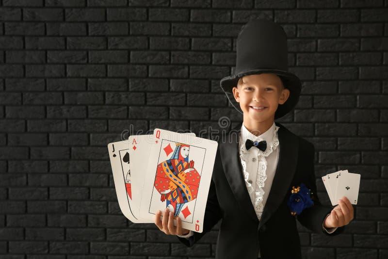 Leuk weinig tovenaar met kaarten tegen donkere bakstenen muur stock fotografie