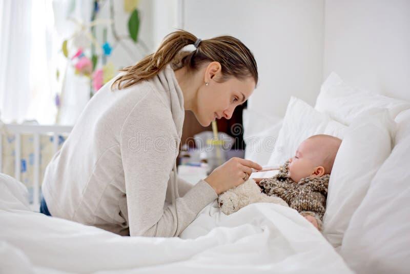 Leuk ziek kind, babyjongen, die in bed, mamma blijven die hem medici geven stock foto's