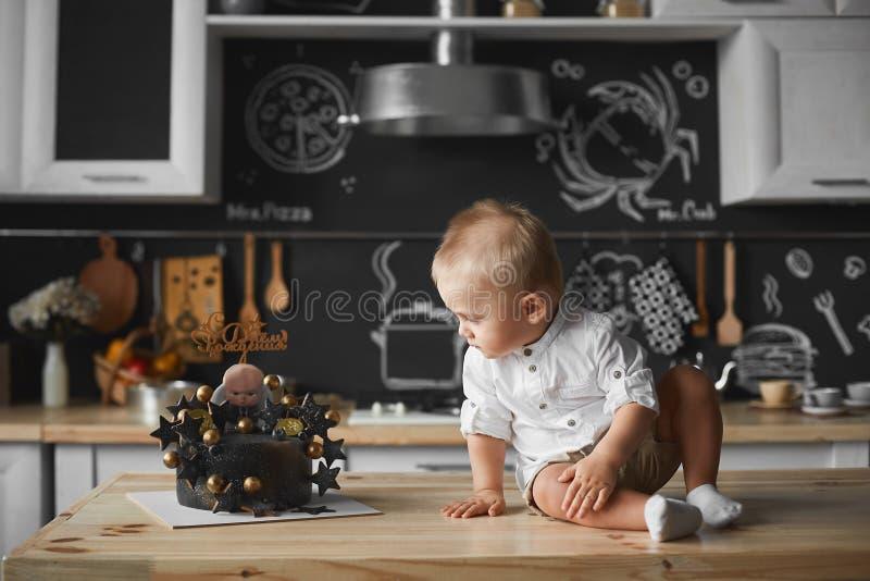 Leuk zit weinig babyjongen op de lijst bij het keukenbinnenland royalty-vrije stock foto