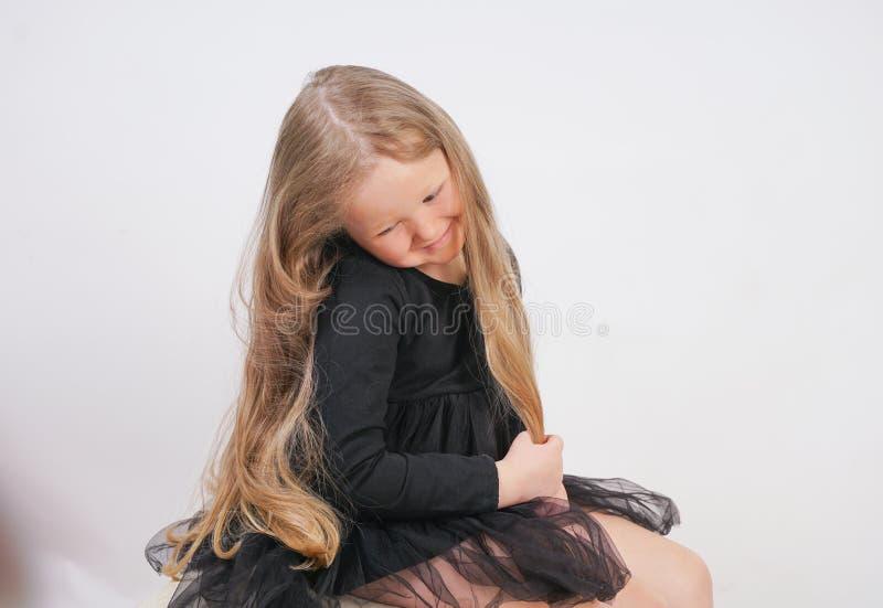 Leuk zit weinig babymeisje met lang blondehaar en raakt haar haar op witte achtergrond stock afbeelding