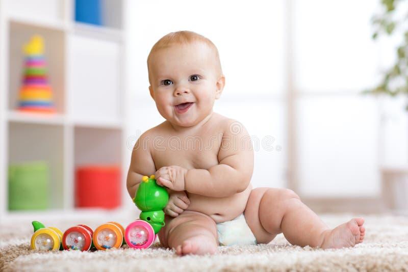 Leuk zit weinig Kaukasische jongen 8 maanden oud en speelt met speelgoed in kinderdagverblijfruimte royalty-vrije stock foto