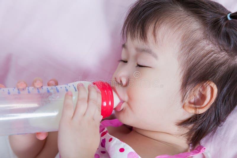 Leuk zuigt weinig Aziatische (Thaise) meisjesslaap en omhoog melk stock foto