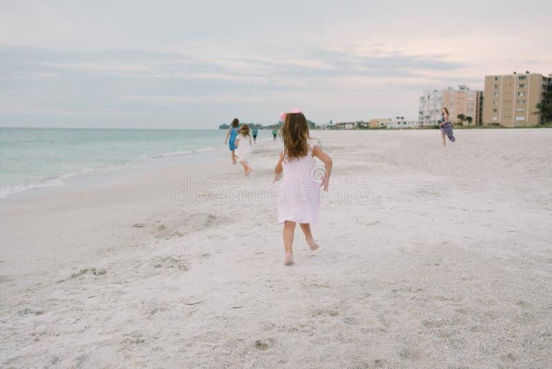 Leuke Aanbiddelijke Gelukkige Jonge Meisjes die in Mooie Kleding op Vakantie bij het Tropische Strand door het Water op Bestemmin stock afbeeldingen