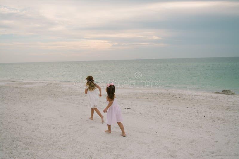 Leuke Aanbiddelijke Gelukkige Jonge Meisjes die in Mooie Kleding op Vakantie bij het Tropische Strand door het Water op Bestemmin royalty-vrije stock afbeelding