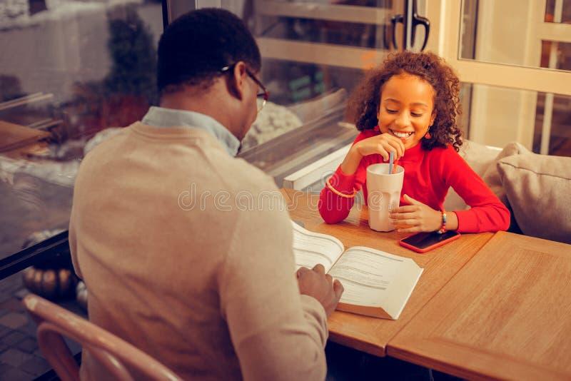 Leuke aantrekkelijke dochter die terwijl consumptiemelkcocktail glimlachen stock afbeelding