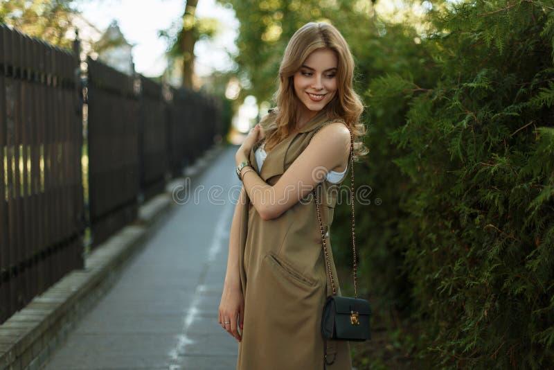 Leuke aantrekkelijke jonge vrouw in een modieuze de zomerkleding met het zwarte leerhandtas stellen op de straat dichtbij groene  royalty-vrije stock afbeelding