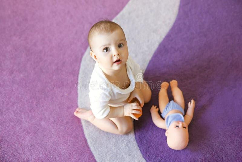 Leuke aardig weinig zitting van het babymeisje op purper tapijt met pop stock afbeelding
