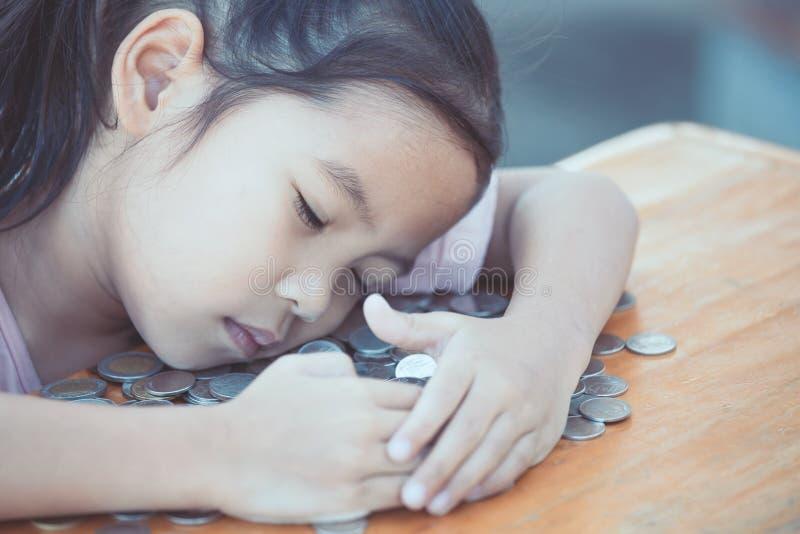 Leuke Aziaat weinig en vrekkig kindmeisje die haar geld koesteren stock foto