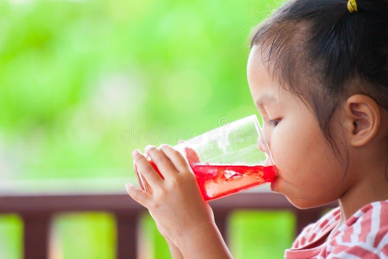 Leuke Aziaat weinig kindmeisje die rood sapwater drinken royalty-vrije stock afbeeldingen