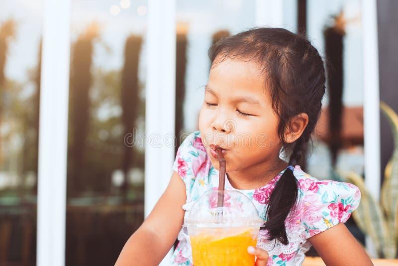Leuke Aziaat weinig kindmeisje het drinken jus d'orange stock foto