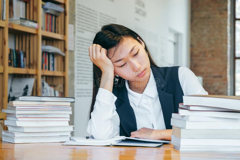 Leuke Aziatische die meisjeszitting in de bibliotheek, door boeken wordt omringd, die van school rusten Een tienerstudent treft v stock afbeeldingen
