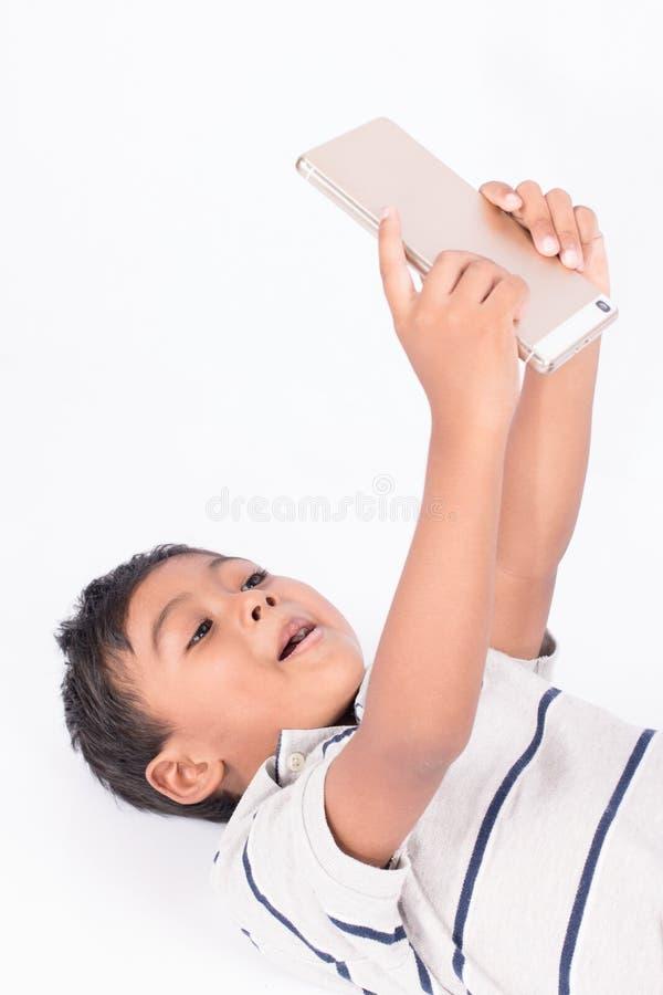 Leuke Aziatische jongen het liggen spelsmartphone stock fotografie