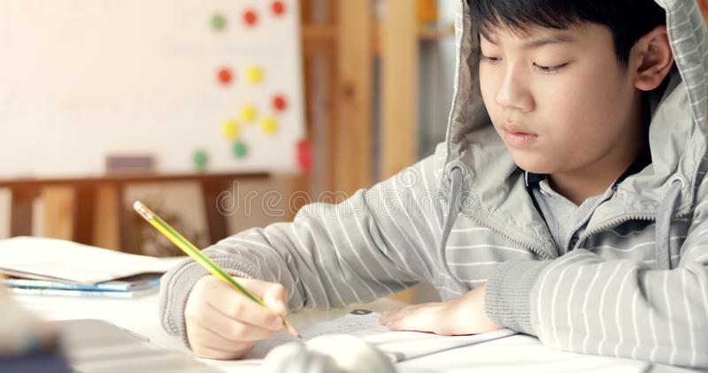 Leuke Aziatische tienerjongen die uw thuiswerk thuis doen stock foto's