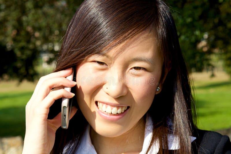 Leuke Aziatische vrouw op telefoon gelukkig glimlachen stock foto