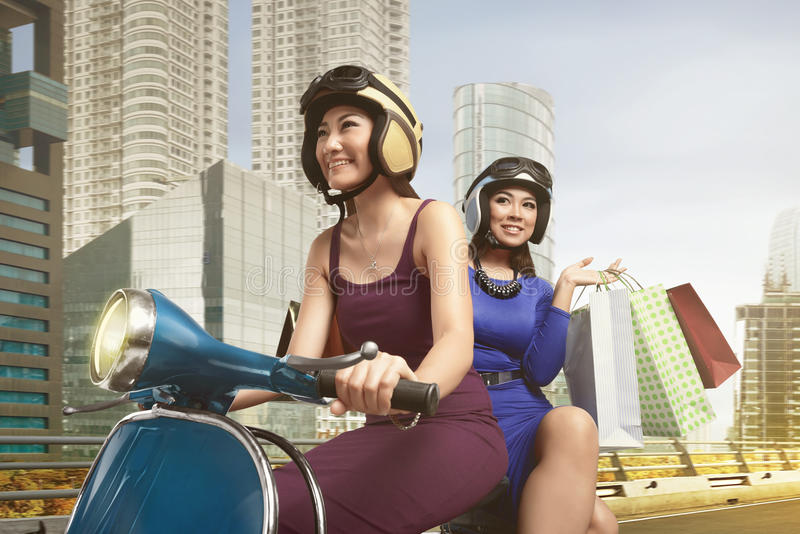 Leuke Aziatische vrouw twee die een autoped berijden stock fotografie