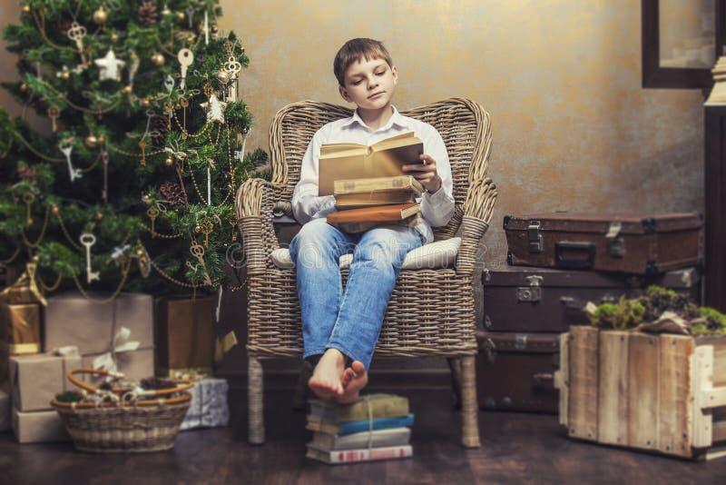Leuke baby als voorzitter die een boek in binnenland lezen stock afbeeldingen