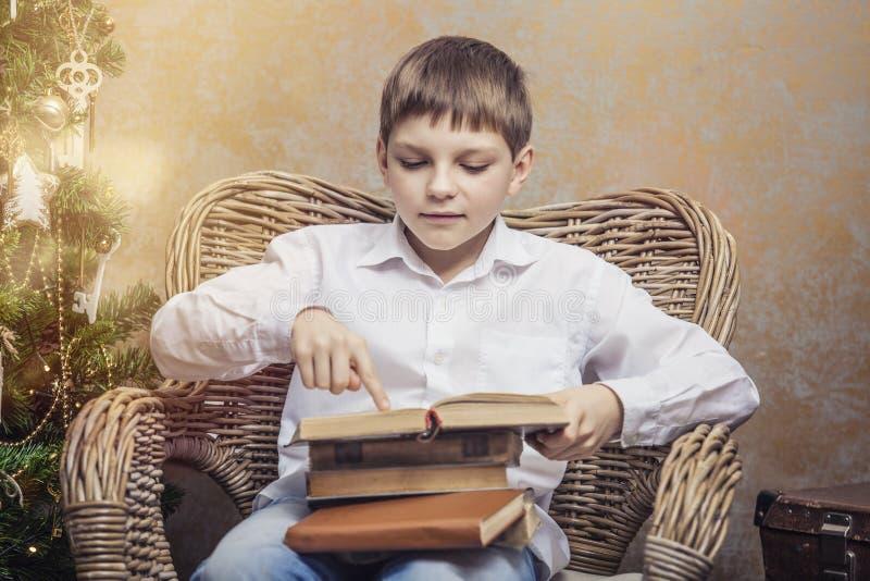 Leuke baby als voorzitter die een boek in binnenland lezen royalty-vrije stock afbeelding