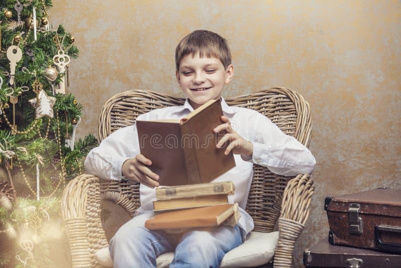 Leuke baby als voorzitter die een boek in binnenland lezen stock foto's