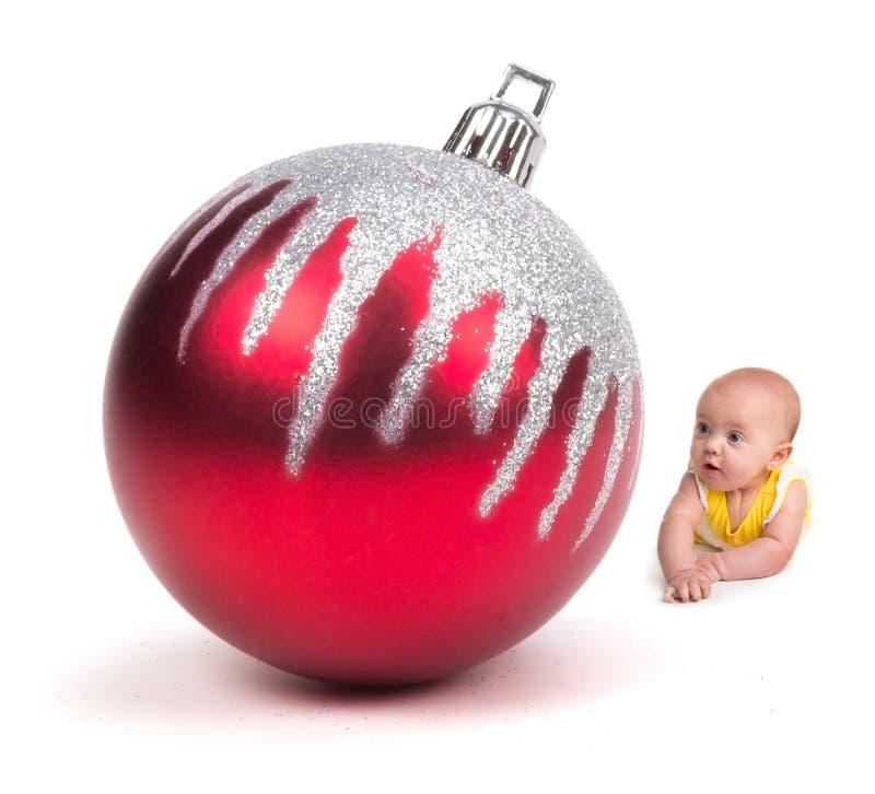 Leuke Baby die bij een Reusachtig Kerstmisornament glimlachen op wit stock afbeeldingen