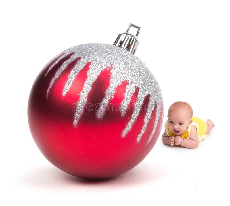 Leuke Baby die bij een Reusachtig Kerstmisornament glimlachen op wit royalty-vrije stock fotografie