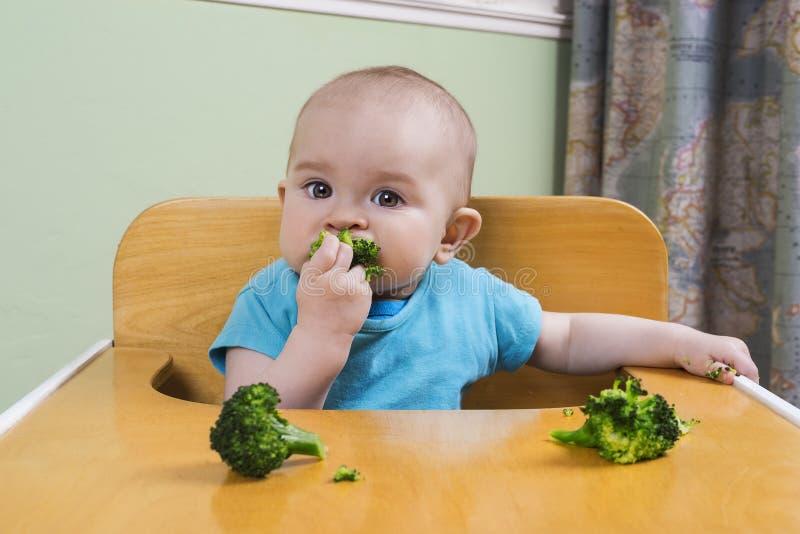 Leuke baby die broccoli eten stock afbeelding