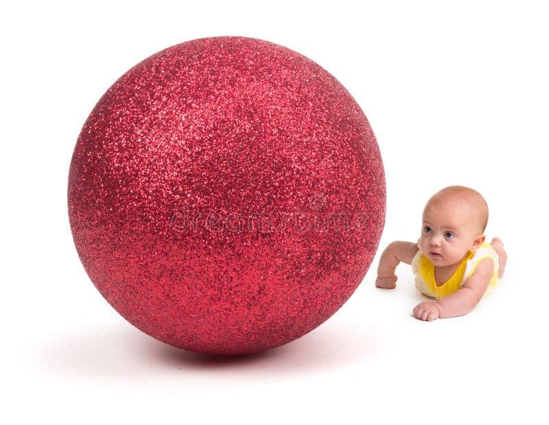 Leuke Baby die een Reusachtig Kerstmisornament bekijken op wit stock foto