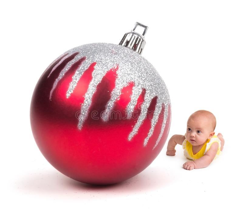 Leuke Baby die een Reusachtig Kerstmisornament bekijken op wit royalty-vrije stock foto's