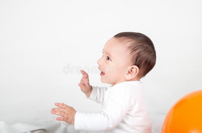 Leuke baby die en met omhoog handen spelen glimlachen stock foto's