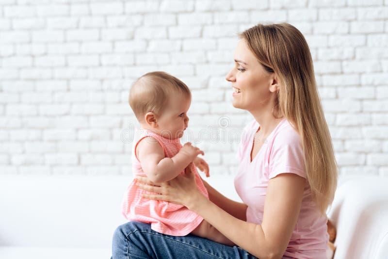Leuke baby die met jonge glimlachende moeder koesteren stock afbeelding