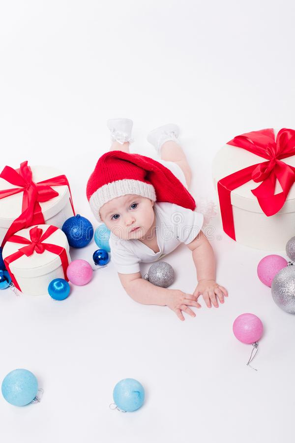 Leuke baby die op zijn maag in een Nieuwjaar ` s GLB liggen onder Christm stock afbeeldingen
