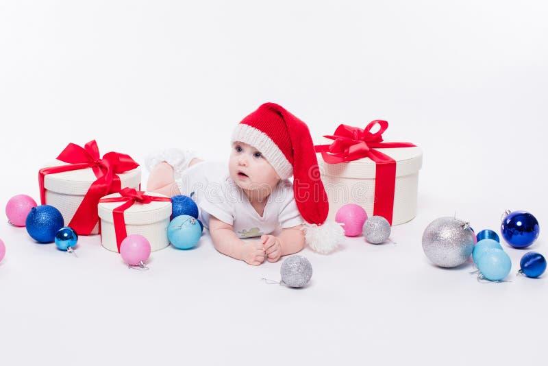 Leuke baby die op zijn maag in een Nieuwjaar ` s GLB liggen onder Christm royalty-vrije stock foto's