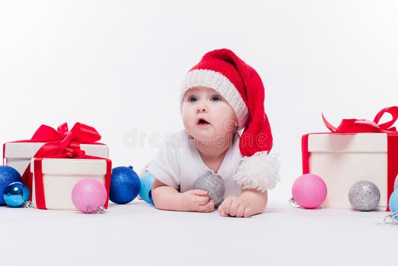 Leuke baby die op zijn maag in een Nieuwjaar ` s GLB liggen onder Christm stock fotografie