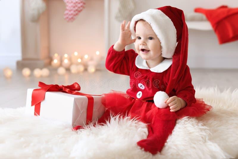 Leuke baby in Kerstmiskostuum en giftdoos op vloer stock afbeeldingen