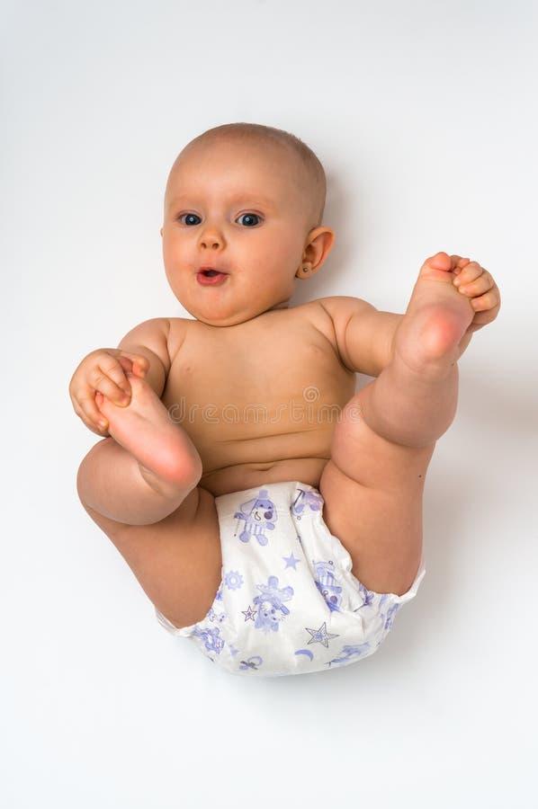 Leuke baby in luier die die op rug liggen - op wit wordt geïsoleerd stock afbeelding