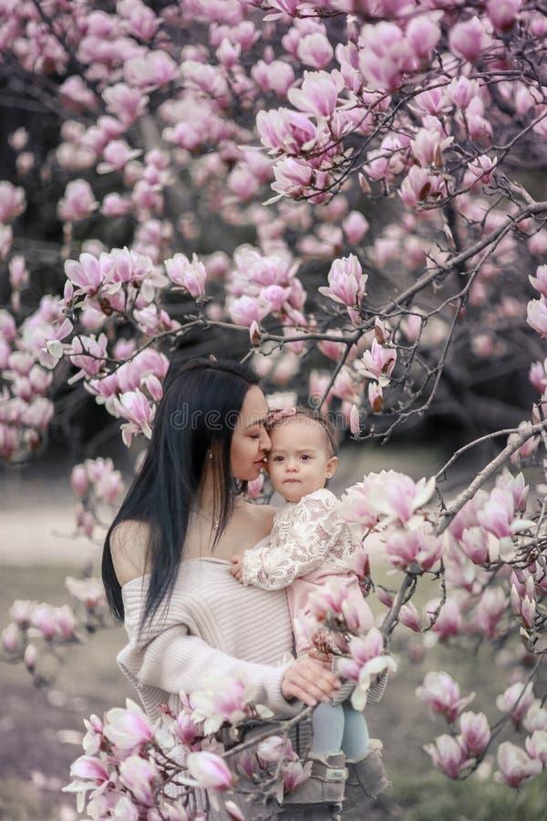 Leuke Baby 6 maand oud Meisje in Roze Uitrusting met Big Blue-Ogen met Jonge Mooie Moeder bij de Lente, Roze Bloeiende Boom royalty-vrije stock fotografie