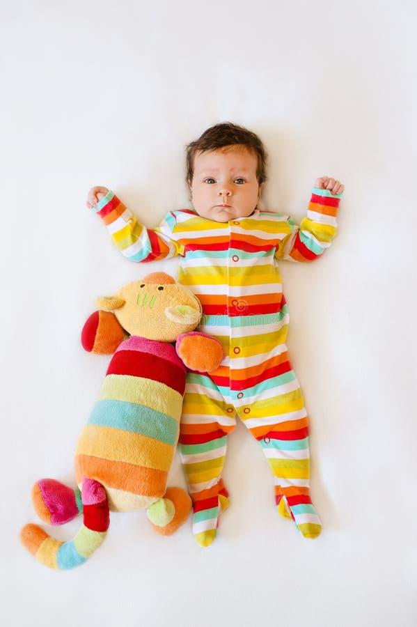 Leuke baby met Gestreepte gekleurde pyjama's en een kattenstuk speelgoed die op bed liggen stock afbeelding