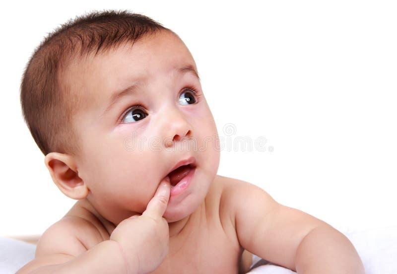 Leuke baby met vinger in zijn mond stock afbeelding
