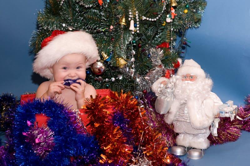 Leuke Baby in rode hoed voor Kerstboom stock fotografie