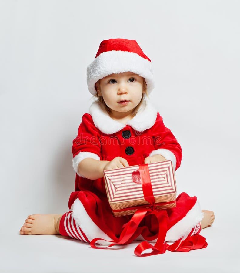 Leuke baby in santahoed het openen de doos van de Kerstmisgift stock foto's