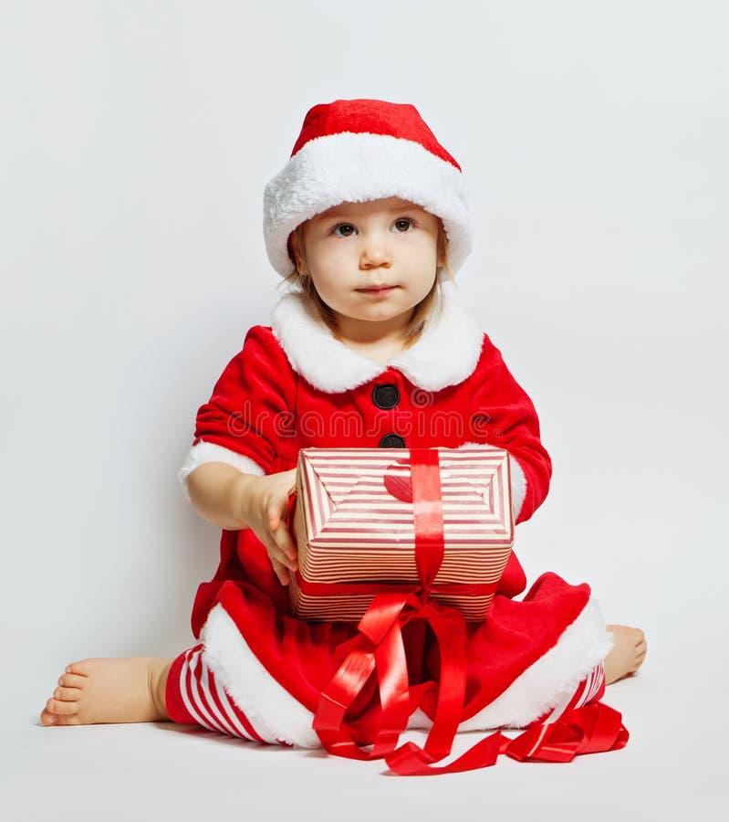 Leuke baby in santahoed met de doos van de Kerstmisgift stock afbeeldingen