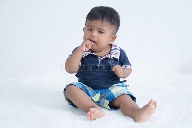 Leuke baby zuigende vinger stock foto
