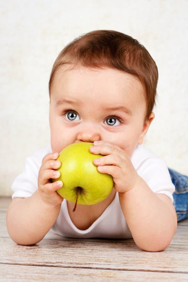 Leuke babyjongen die appel eten stock fotografie
