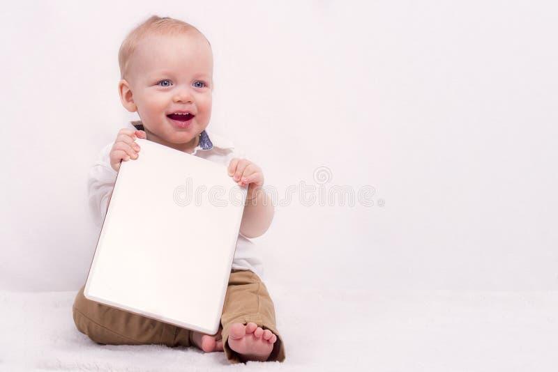 Leuke babyjongen die een banner houden tegen witte achtergrond De ruimte van het exemplaar stock fotografie