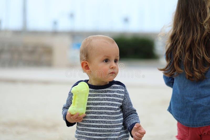 Leuke Babyjongen die een Sweater op Sandy Beach dragen stock fotografie